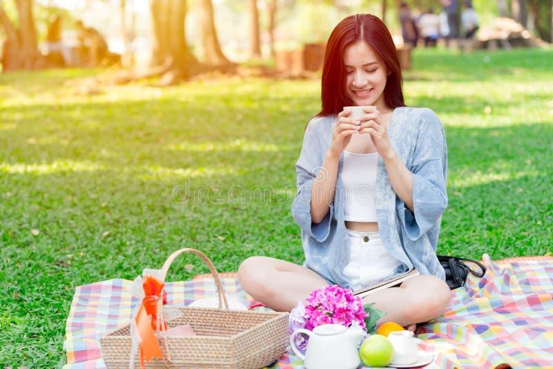 Den härliga asiatiska kvinnainnehavkoppen som in dricker, parkerar medan picknicken royaltyfri foto