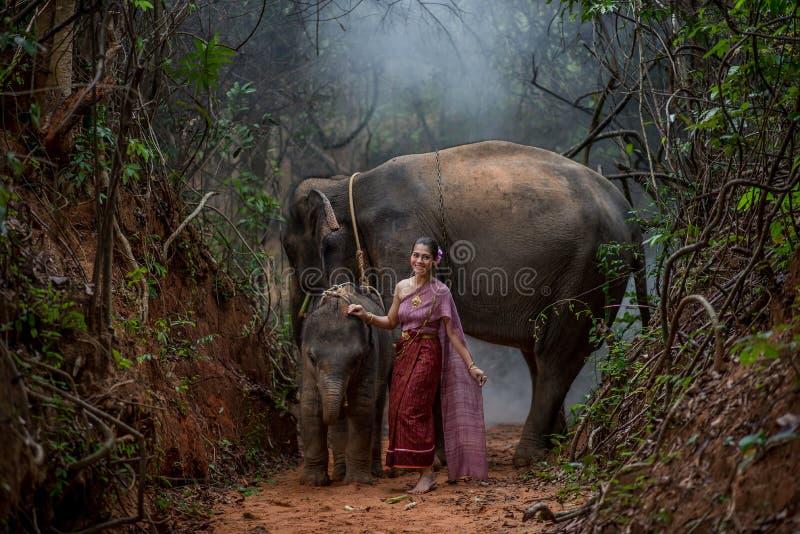 Den härliga asiatiska kvinnan bär den thai klänningen med hennes elefant, elepha royaltyfri foto