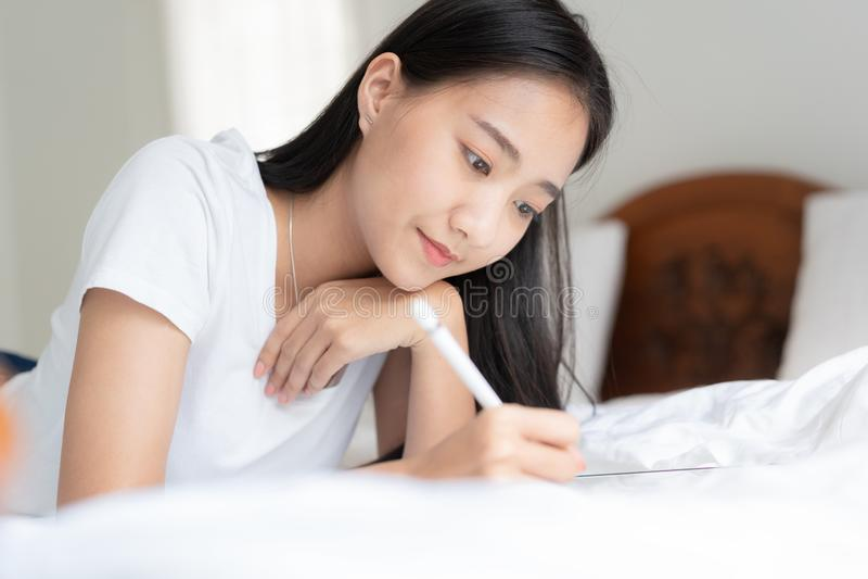 Den härliga asiatiska kvinnan drar på sängen Asiatisk flicka som använder minnestavlan för att lära att dra på hennes hem royaltyfria foton