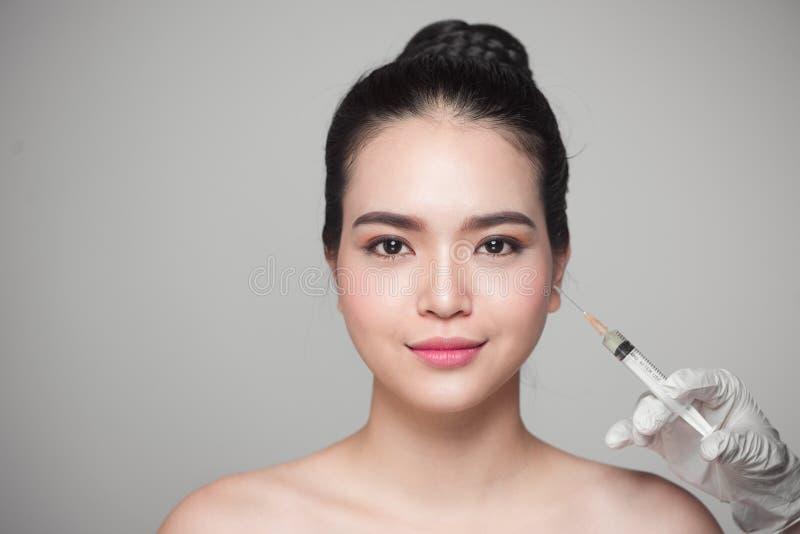 Den härliga asiatiska kvinnan får skönhetansiktsbehandlinginjektioner Åldras för framsida arkivfoton