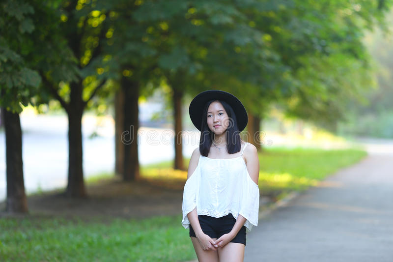Den härliga asiatiska kvinnan i en hatt ser in i kameraståenden fotografering för bildbyråer