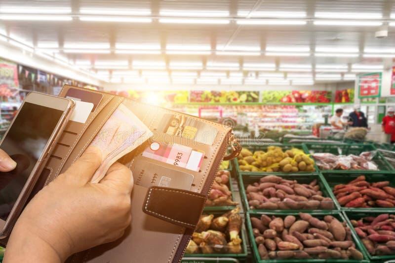 Den härliga asiatiska kvinnan i supermarketshopping med kreditkorten och kortinnehavare lånar fonder med som att betala för gods  royaltyfria foton