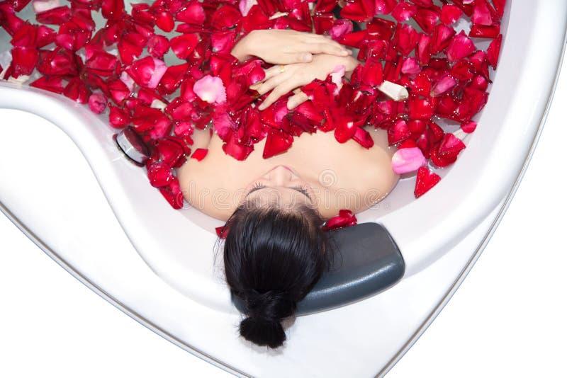Den härliga asiatiska kvinnan tar ett bad i bubbelpool med rosa kronblad arkivbild