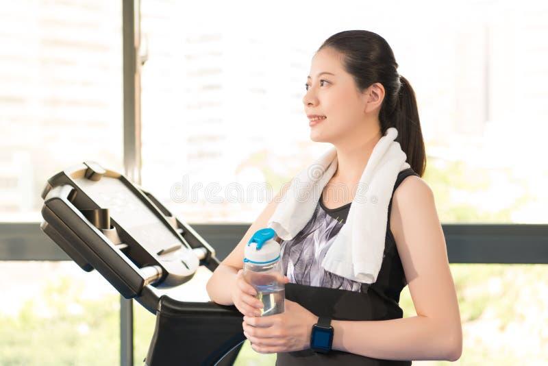 Den härliga asiatiska kvinnan vilar den hållande vattenflaskan efter trampkvarn royaltyfria foton