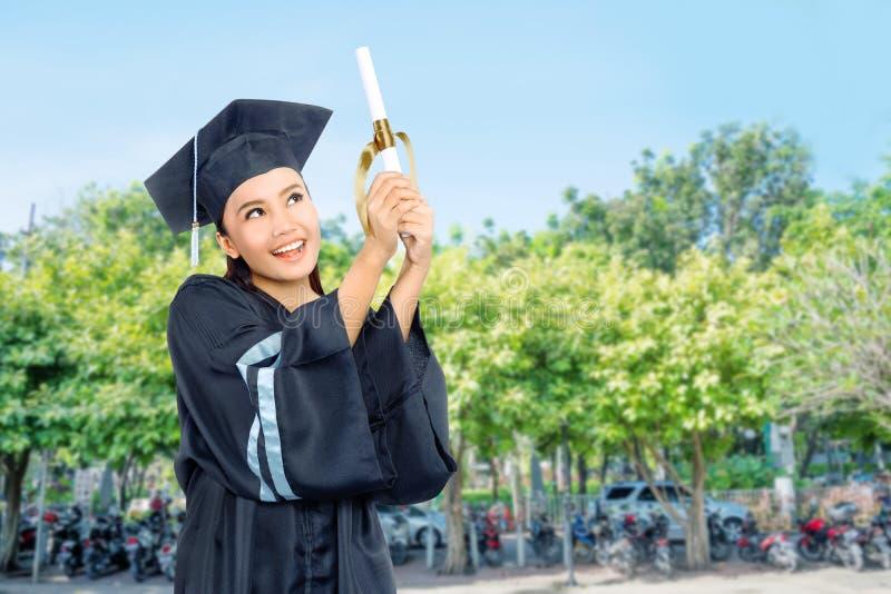 Den härliga asiatiska studentflickan firar hennes avläggande av examen med lock a royaltyfri bild