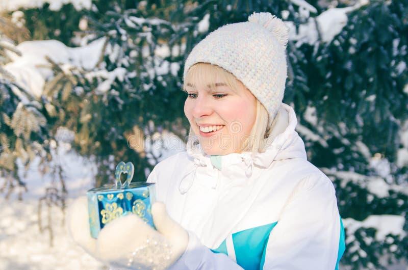 Den härliga attraktiva blonda flickan jublar i en ask med en gåva t royaltyfri foto