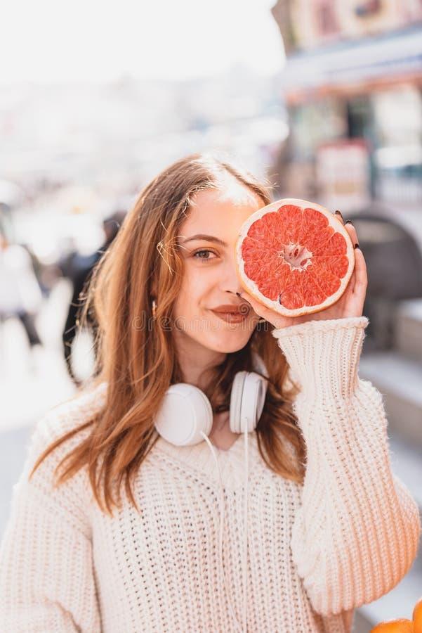 Den härliga attraktiva unga flickan rymmer halva av citrusfrukt arkivfoto