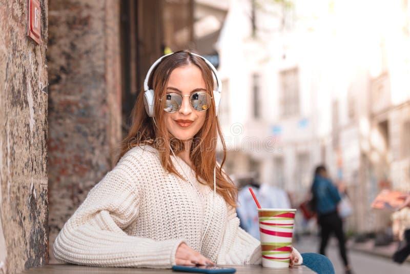 Den härliga attraktiva unga flickan sitter ett kafé arkivfoton