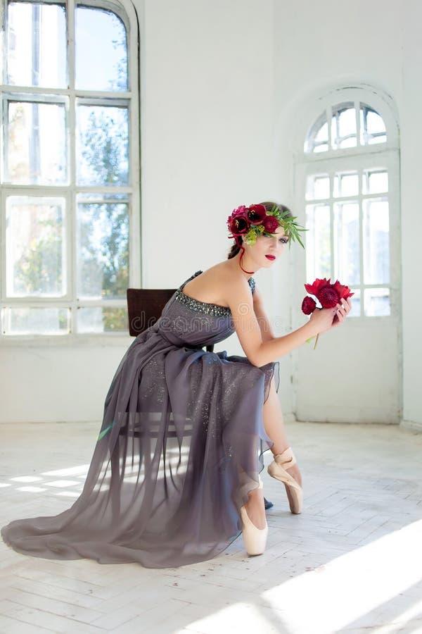 Den härliga ballerina som sirtting i långa grå färger arkivfoton