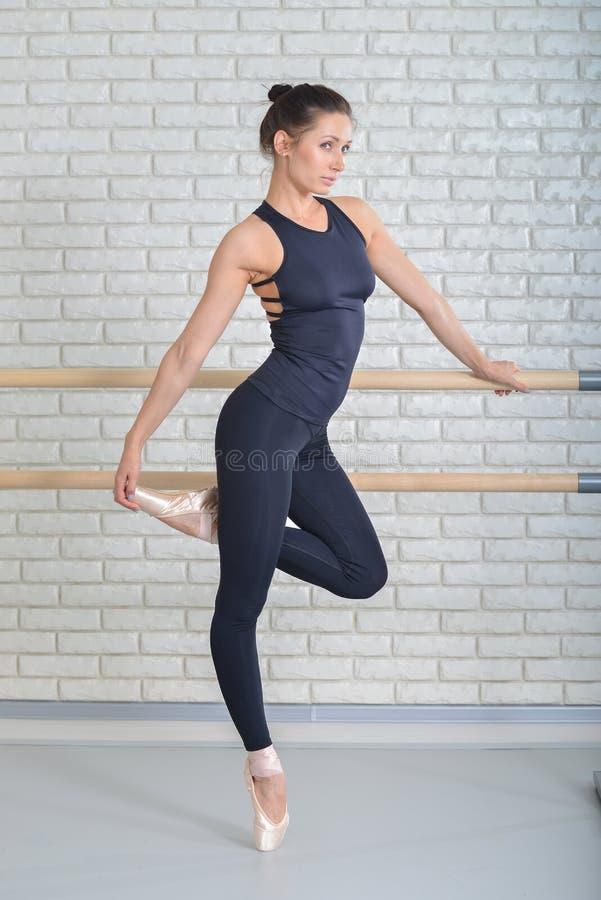 Den härliga ballerina weared i svarta bodysuit- och vitpointeskor som poserar på balett, klassificerar nära barren, full längd arkivbild