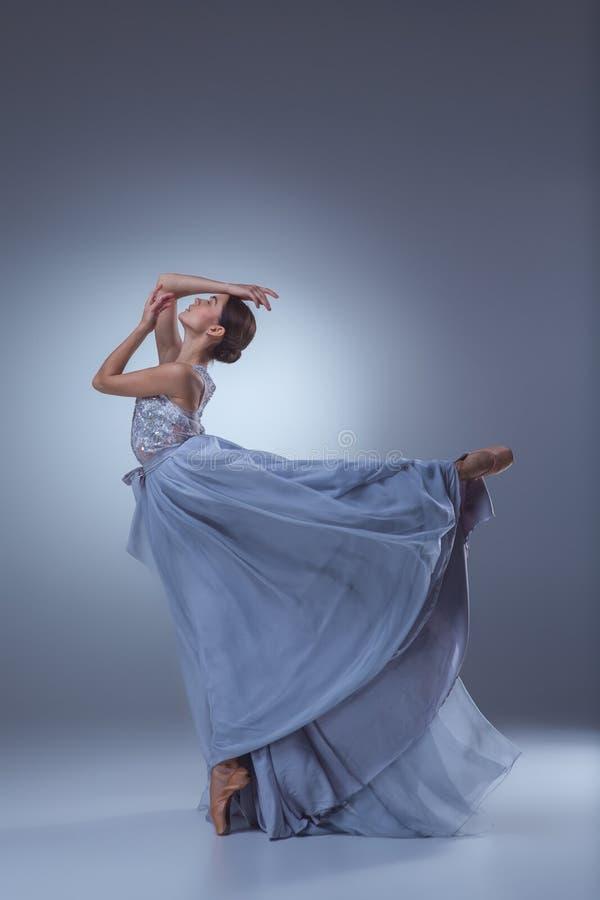 Den härliga ballerinadansen i blå lång klänning royaltyfri fotografi