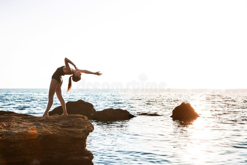 Den härliga ballerinadansen som poserar på, vaggar på stranden, havsbakgrund royaltyfri foto