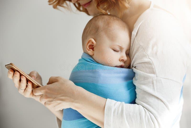 Den härliga barnmodern läser artiklar om moderskapliv på telefonen medan den lilla älskvärda sonen som in sover på hennes bröstko arkivbild