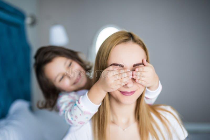 Den härliga barnmodern och hennes lilla unga dotter ler på säng hemma Flickan stänger hennes moderögon royaltyfri fotografi