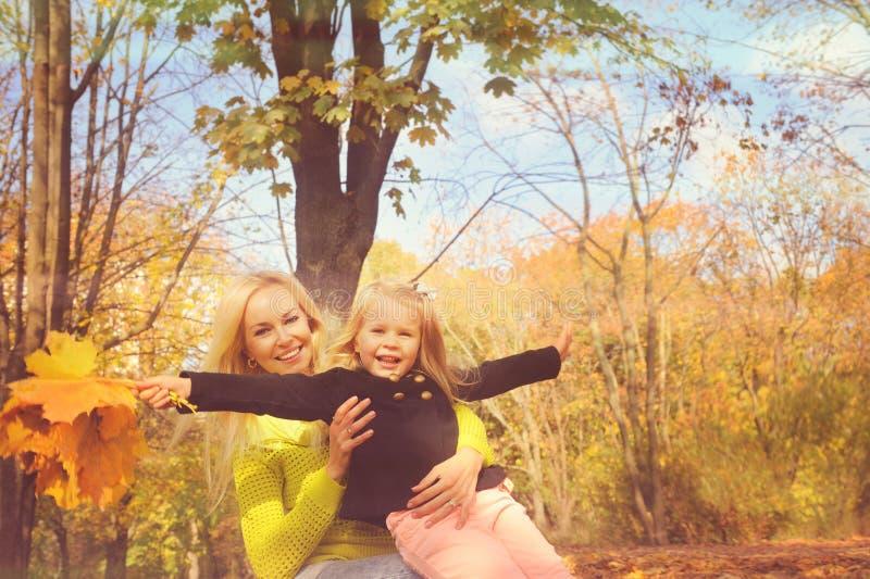Den härliga barnmodern och lilla dottern som tillsammans spelar i, parkerar fotografering för bildbyråer