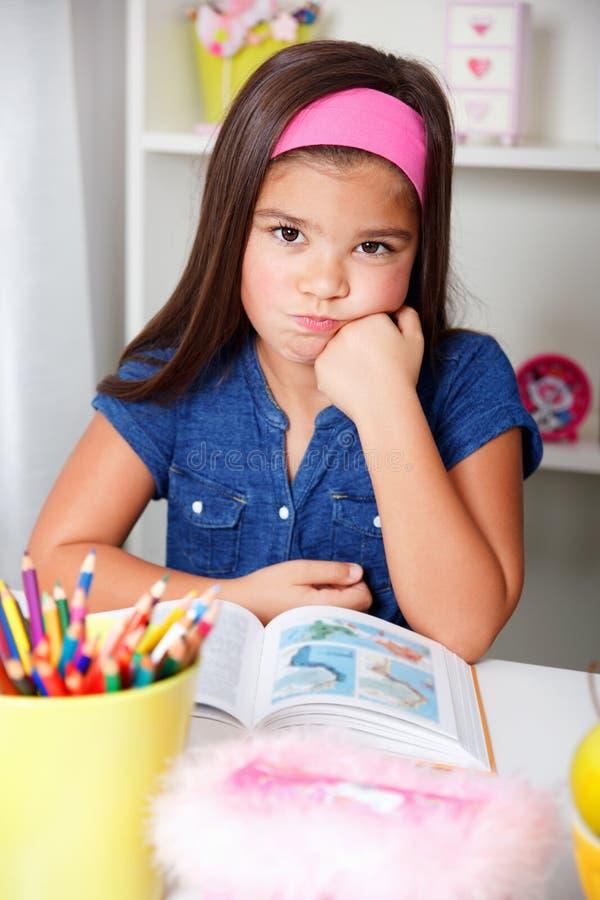 Den härliga barnskolaflickan är sjuk av att lära arkivfoton