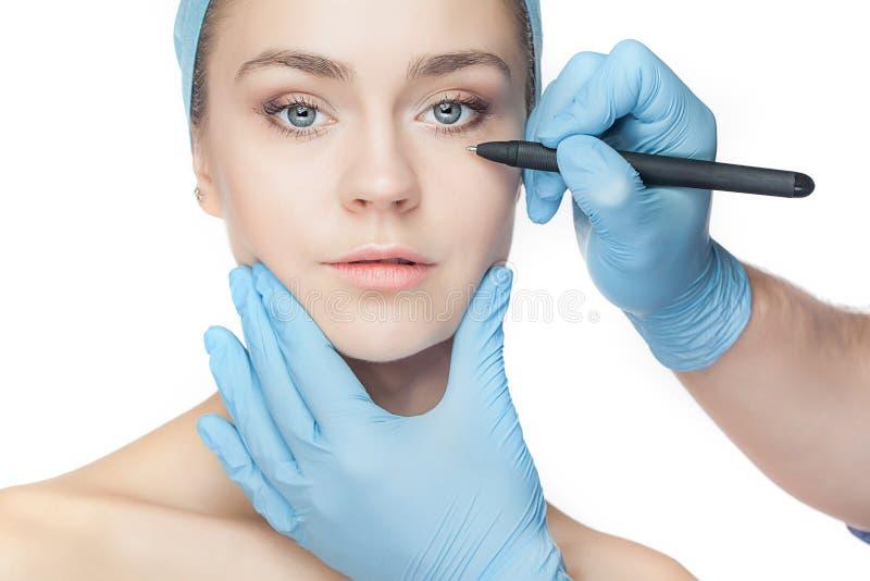 den härliga beauticianen vänder henne mot linjer funktionsperforeringsplastikkirurgi som trycker på kvinnabarn fotografering för bildbyråer