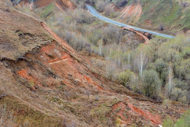 Den härliga bergvägen går upp En slingrig huvudväg som sträcker in i avståndet mot bakgrunden av en härlig vår royaltyfri bild
