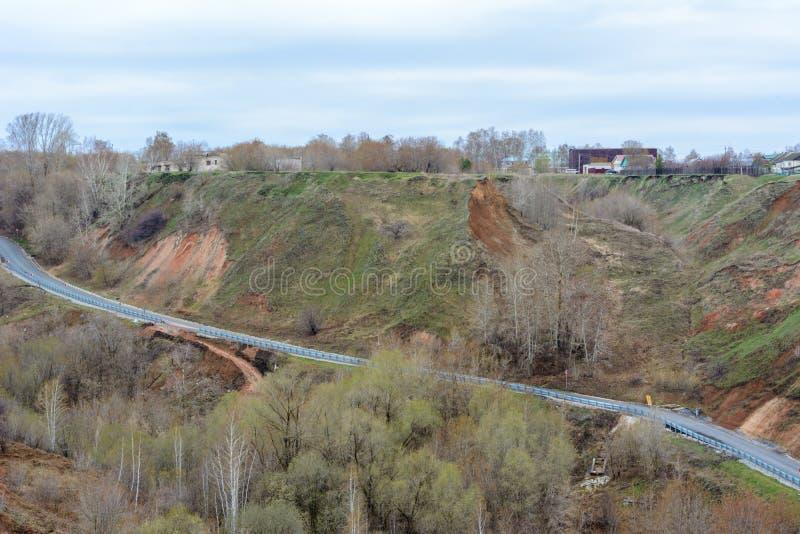 Den härliga bergvägen går upp En slingrig huvudväg som sträcker in i avståndet mot bakgrunden av en härlig vår arkivfoto