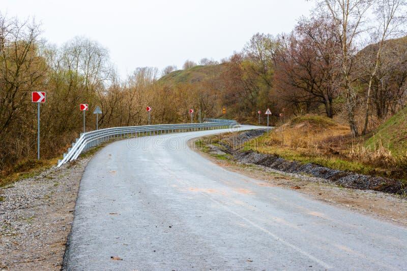 Den härliga bergvägen går upp En slingrig huvudväg som sträcker in i avståndet mot bakgrunden av en härlig vår royaltyfri fotografi