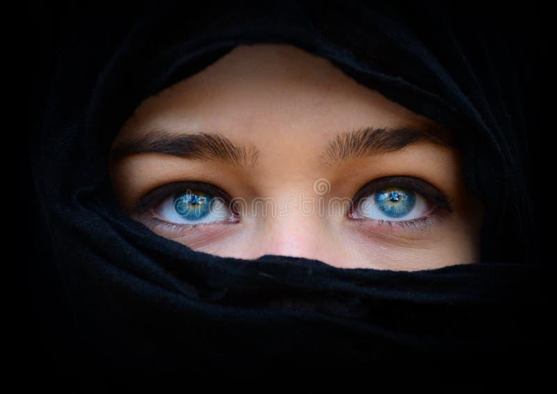 Den härliga blåa kvinnan synar bak den svarta halsduken som ser upp arkivfoton