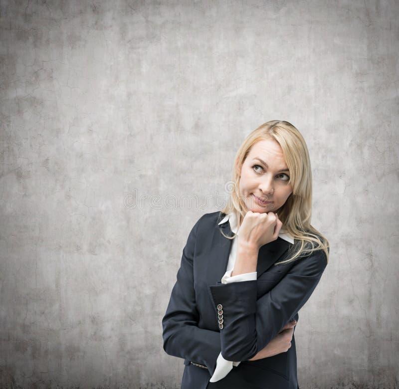 Den härliga blonda affärskvinnan tänker om affärsfrågor royaltyfri fotografi