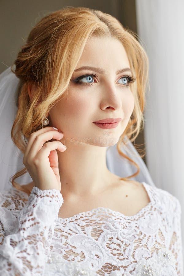 Den härliga blonda bruden i morgonen i en vit bröllopsklänning med skyler på hennes huvud, ståenden av bruden för bröllopet arkivfoto
