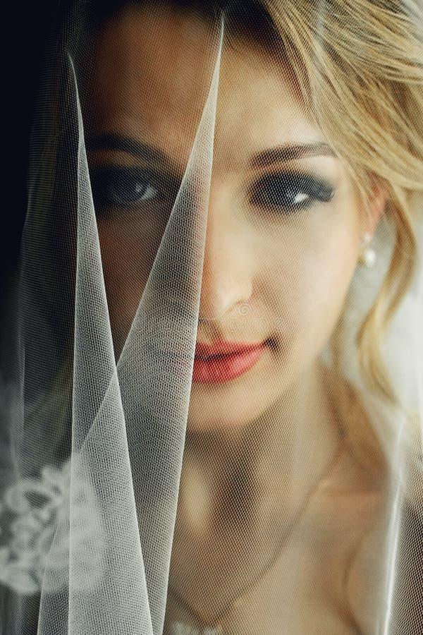 Den härliga blonda bruden i smink och skyler i vita clos för en klänning arkivfoto