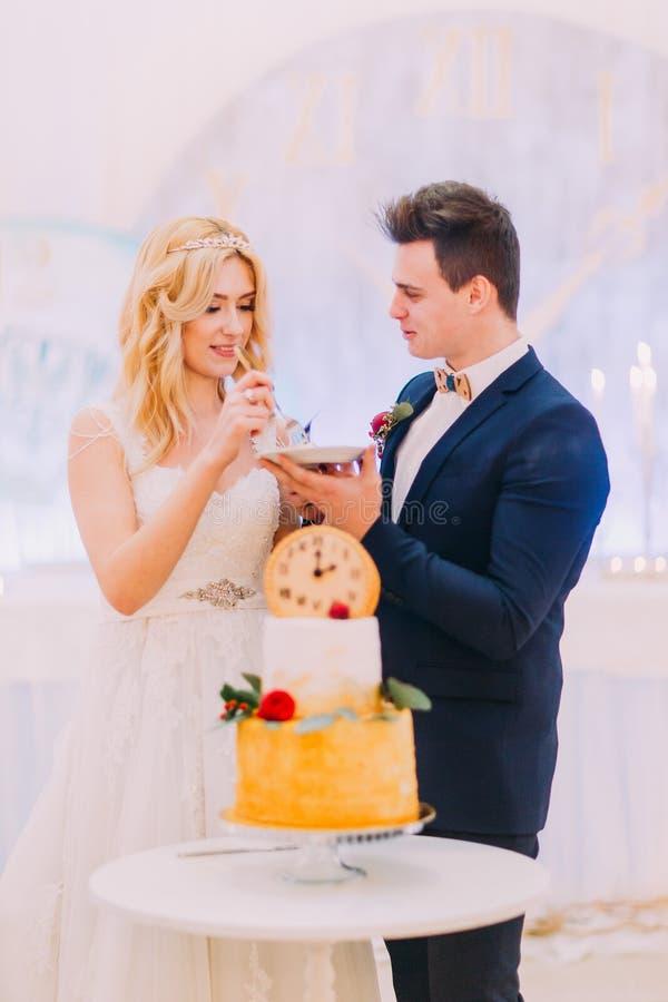 Den härliga blonda bruden och brudgummen äter bröllopstårtan tillsammans arkivbild