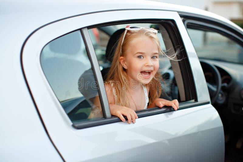 Den härliga blonda flickan 5 år sticker fram ut ur det bilfönstret fotografering för bildbyråer