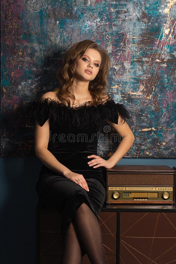 Den härliga blonda flickan bär den trendiga klänningen som poserar på studion med den retro fmmottagaren arkivbild