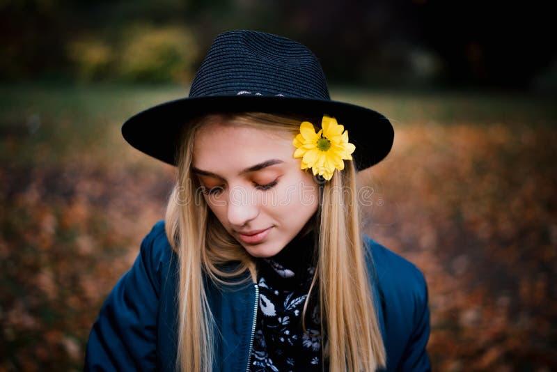 Den härliga blonda flickan i en hatt och i blått omslag med den gula blomman i höst parkerar fullt av gula sidor arkivbilder