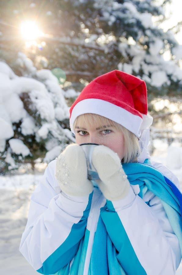 Den härliga blonda flickan i en röd julhatt dricker varmt te från en kopp Lodlinjen beskådar arkivbilder