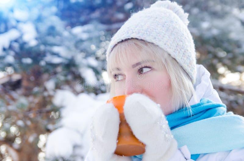 Den härliga blonda flickan i hatt dricker varmt te från koppen arkivfoto