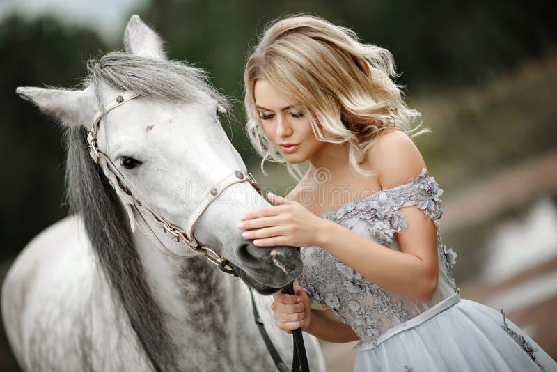 Den härliga blonda flickan i klänning slår en grå häst på naturen in royaltyfri bild