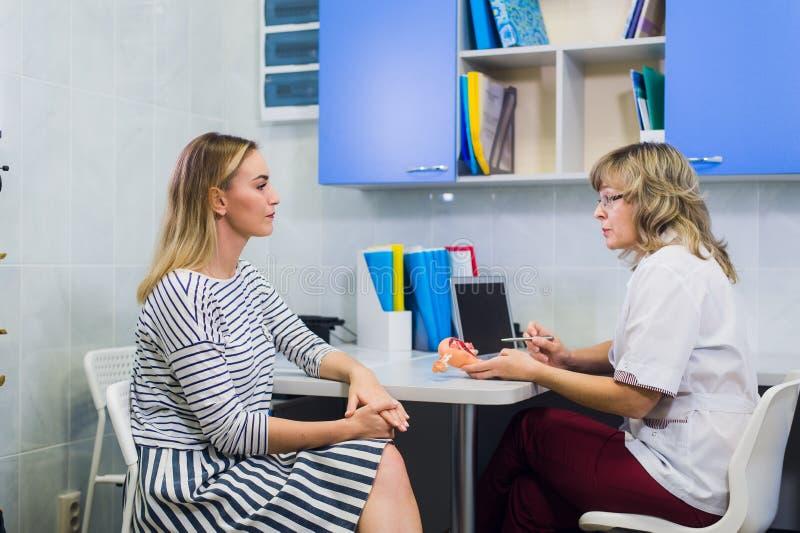 Den härliga blonda flickan konsulterar med en doktor royaltyfri bild