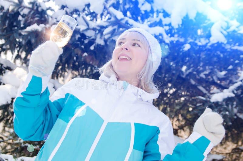 Den härliga blonda flickan med ett exponeringsglas av champagne sjunger och dansar utomhus på en bakgrund av snöig gran-träd i vi arkivfoton