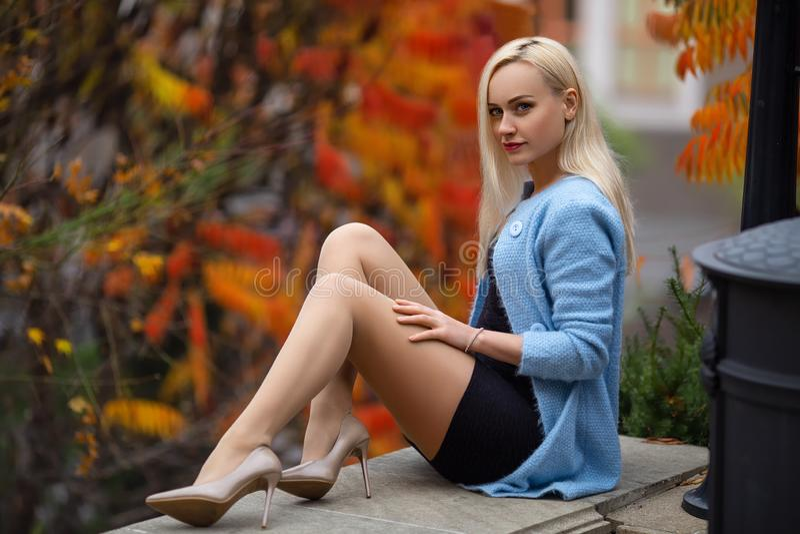 Den härliga blonda flickan med perfekta ben och blått posera för blus som är utomhus- på gatan av hösten, parkerar i ljusen av in royaltyfri fotografi