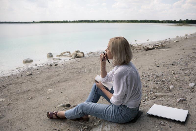 Den härliga blonda flickan sitter på kusten royaltyfria bilder