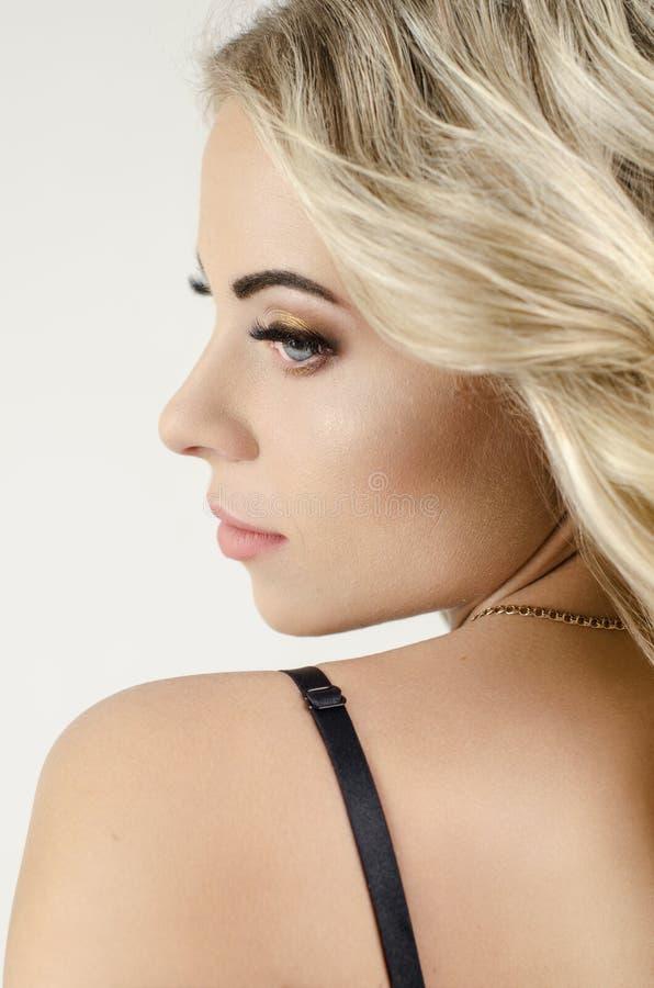 Den härliga blonda flickan snör åt in underkläderna royaltyfri foto