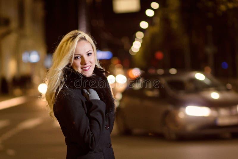 Den härliga blonda kvinnan i bil tänder i nattstaden arkivfoton