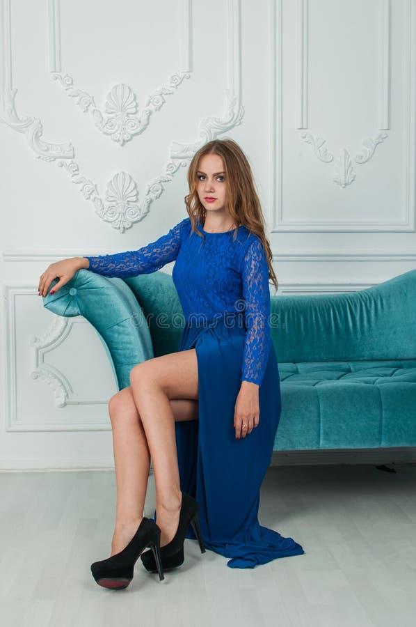 Den härliga blonda kvinnan i blått klär i inre royaltyfri bild