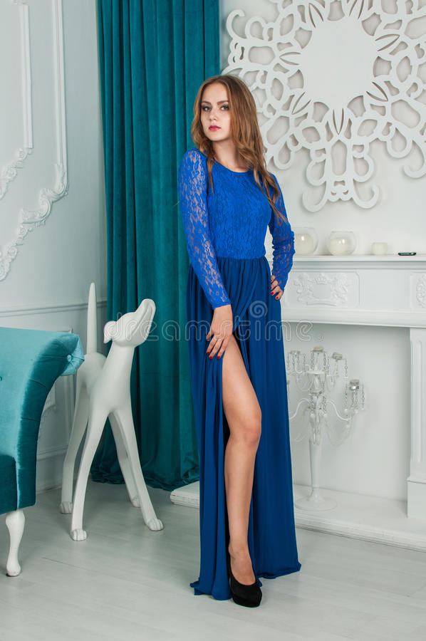 Den härliga blonda kvinnan i blått klär i inre arkivfoto