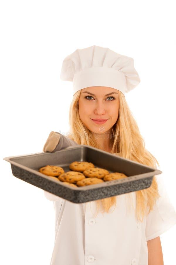 Den härliga blonda kvinnan i kockklänning bakar kakor som över isoleras royaltyfri foto
