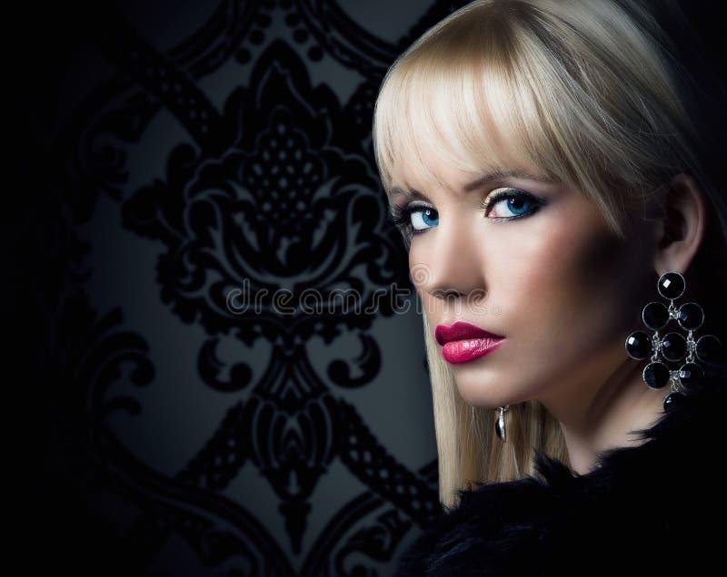 Den härliga blonda kvinnan i lyx pälsfodrar täcker royaltyfria foton