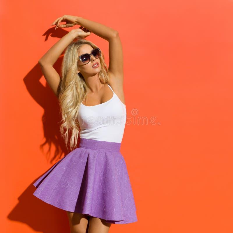 Den härliga blonda kvinnan i solglasögon, den Violet Mini Skirt And White Tank överkanten poserar med lyftta armar arkivbild