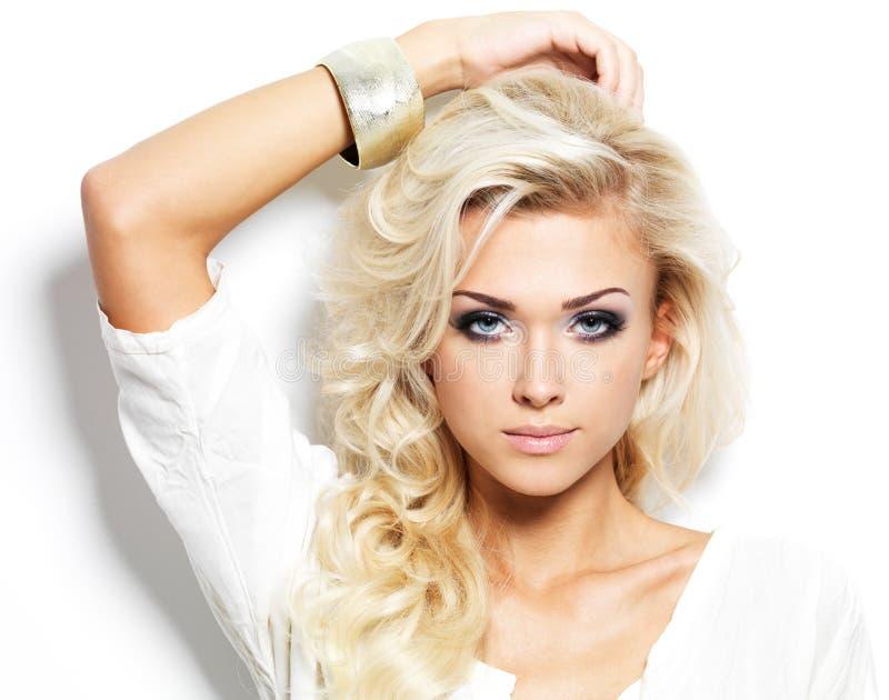 Den härliga blonda kvinnan med långt lockigt hår och utformar makeup. royaltyfri foto