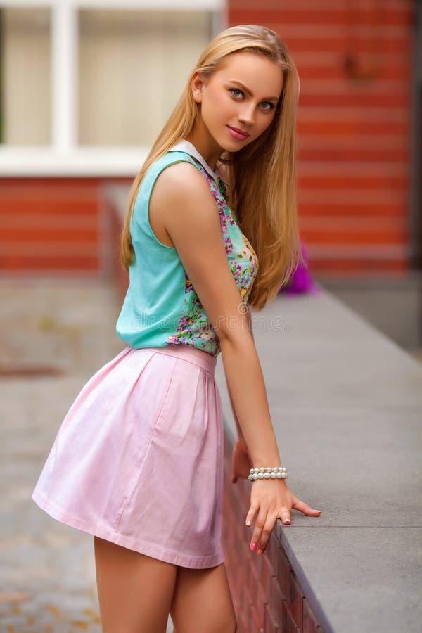 Den härliga blonda kvinnan med rosa färger kringgår att posera som är utomhus- fashion flickan royaltyfri fotografi