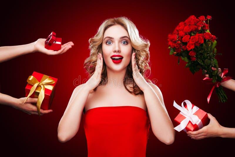 Den härliga blonda kvinnan mottar gåvor och blommor på helgonvalentin och internationella dagar för kvinna` s arkivbilder