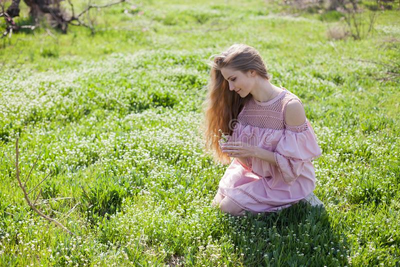 Den härliga blonda kvinnan samlar vårfärg i trädgården arkivbild